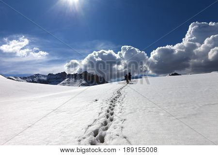 Footpath in snow and two hikers on snowy plateau at sun spring day. Turkey Central Taurus Mountains Aladaglar (Anti-Taurus) plateau Edigel (Yedi Goller)