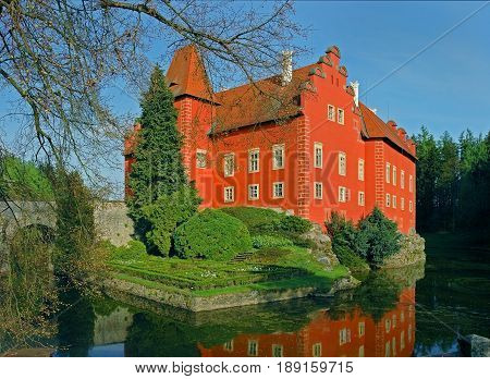 Panoramic view on traditional european antique red castle Cervena Lhota with bridge. Famous Czech Republic Renaissance castles. Red castle among green forest trees, at forest pond. Famous sightseeing