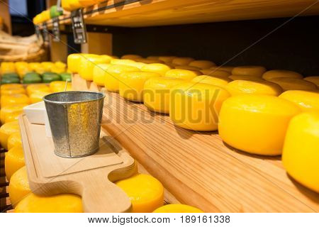 Cheese wheels on wooden shelves. Platter for cheese degustation. Different sort of farm made cheese.