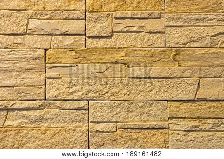 The wall is lined with beige rectangular tiles with a voluminous rough surface.