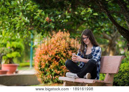Teenage girl sitting on bench using phone and looking upset.