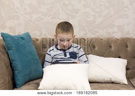 boy sitting on the couch and looking at tablet