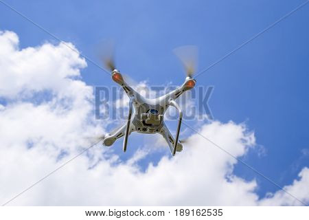 Drone Dji Phantom 4 In Flight. Quadrocopter Against The Blue Sky With White Clouds. The Flight Of Th
