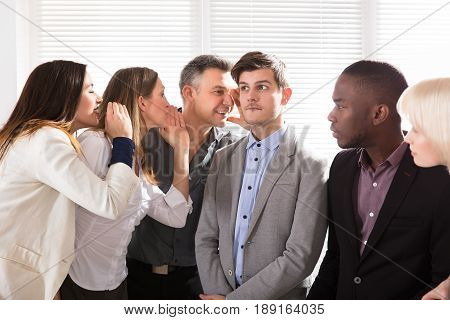 Businesspeople Telling Gossips To The Young Businessman In Office