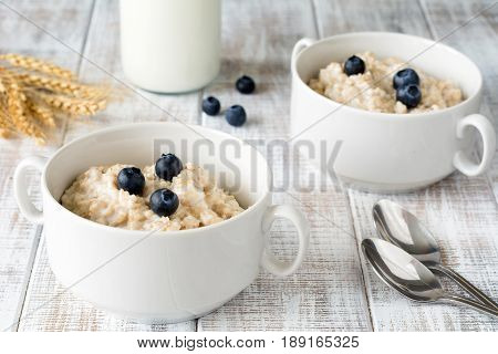 Oatmeal porridge / porridge oats / breakfast cereals with blueberries and bottle of milk on vintage white wooden table. Healthy eating, healthy breakfast food