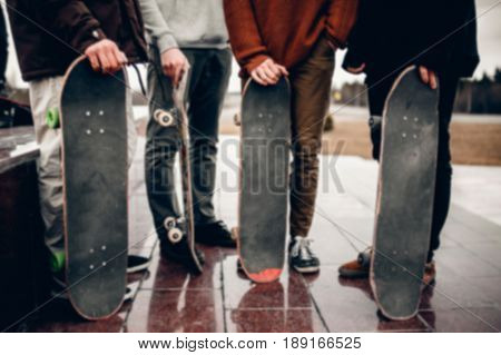 Friends of the men's company hold their hands skateboards. Concept group of street athletes students. Motion blur effect. Bright sunlight.
