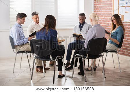Group Of People Sitting On Chair In Circle Reading Bibles