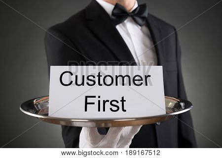 Close-up Of A Male Waiter Holding Tray With Text Customer First On Card