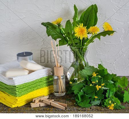 Flowers and leaves of celandine extract in a small bottle soap and bath towel skin care concept selective focus