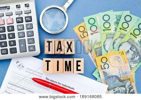 Tax Time - Australia - wooden letters with tax form, magnifying glass, money and calculator