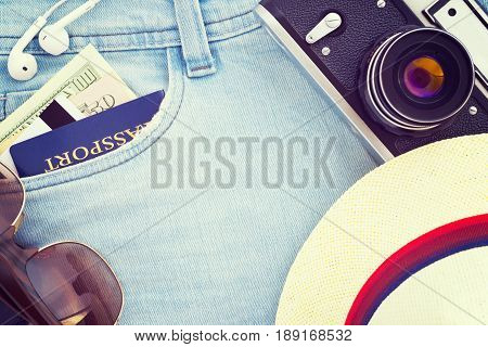 Vacation suite top view; Passport dollar banknotes credit card headphones sunglasses hat retro film photo camera on jeans. Travel top view background; Vintage filter