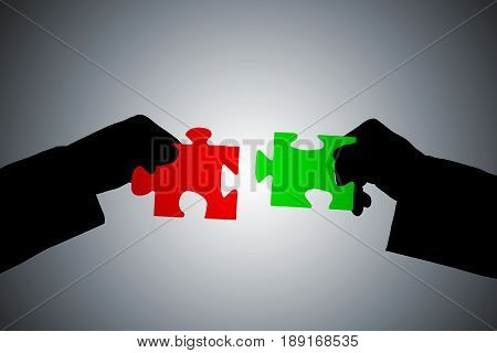 Silhouette Of Hands Putting Green And Red Puzzle Pieces Together Against Gray Background
