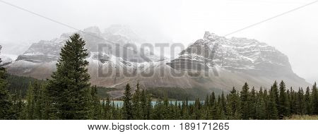 A shot of the beautiful Canadian Rockies along the Bow River obscured by the haze of clouds.