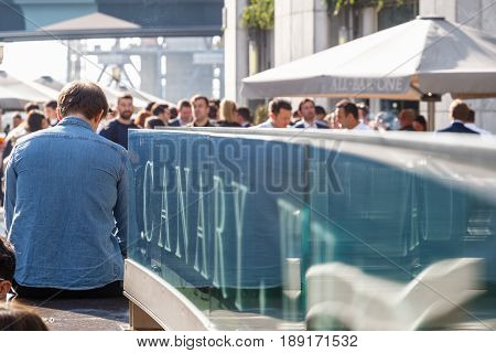 Canary Wharf Sign With A Crowd Of People Drinking At A Dockside Bar In The Background