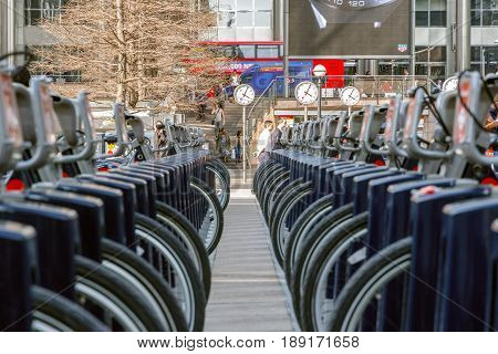 London UK - May 10 2017 - Reuters Plaza in Canary Wharf seen through two rows of Santander cycles at a docking station