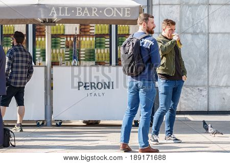 Two Men Drinking Beer Outside A Bar In Canary Wharf On A Sunny Day