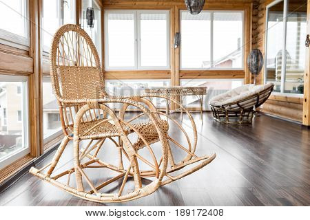 Chair at the balcony. Rattan rocking chairs at wooden balcony