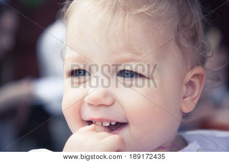 Cute smiling fascinated baby girl portrait with finger in mouth