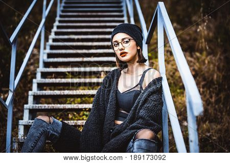 Beautiful fashion model sitting on a staircase