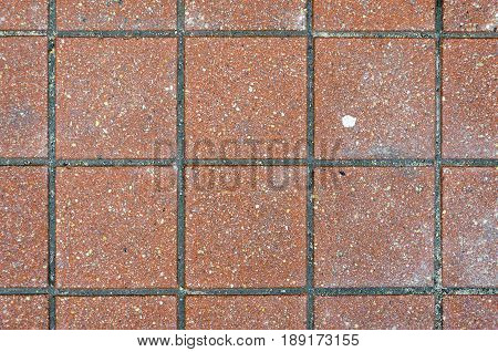 Red brick paving stones on a sidewalk. Abstract background texture