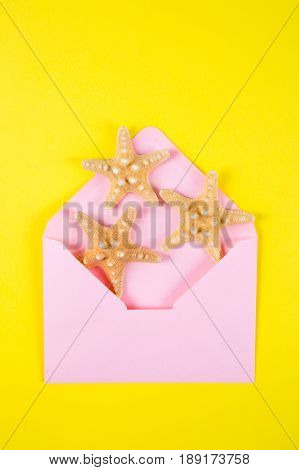 Pink Envelope With Three Starfishes On Colored Yellow Background
