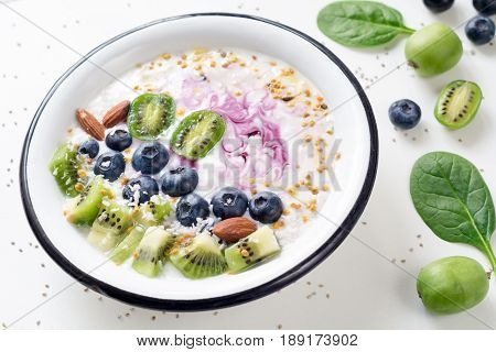 Smoothie bowl with acai berry, kiwi, blueberry, almond, coconut, bee pollen and baby spinach on white background. Healthy detox smoothy bowl for healthy lifestyle
