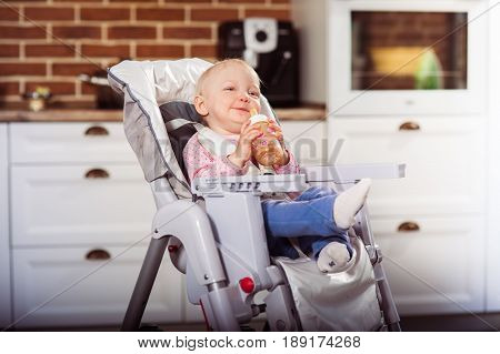 One year toddler girl sits on baby high chair and drinking a juice from plastic bottle. Horizontal