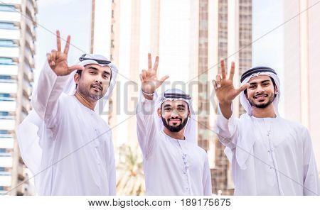 Three arabic men bonding outdoors - Businesspeople walking and talking in Dubai