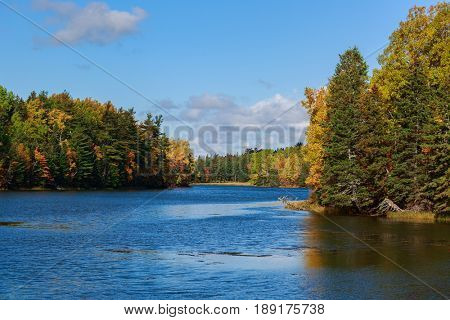 Autumn foliage along a river in rural Prince Edward Island, Canada.