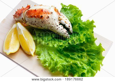 Far Eastern boiled crab lies on a cutting board on a sheet of green salad with lemon wedges, isolate. The concept of seafood in Russia and the Kola Peninsula and Kamchatka.