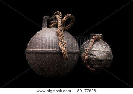Two old fishing net metal balls on black background