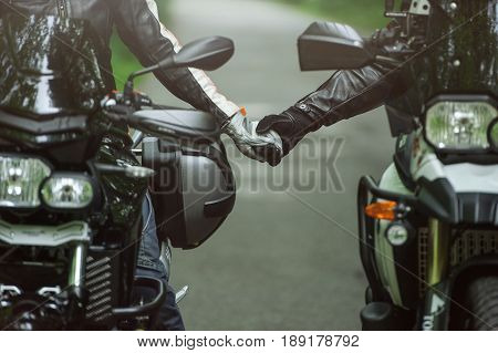 Two Motorcyclists Are Holding Hands While Sitting On Motorcycles