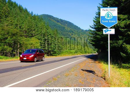 NORTHERN CALIFORNIA, USA - September 3, 2009: Maroon colored minivan speeds by a Pacific Coast Scenic Byway sign