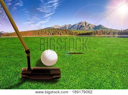 Golfer using a putter club to hit a golf ball on a beautiful golf course with lakes and mountain scenery in the early morning. Deliberate lens flare. 3D rendering of golf course.