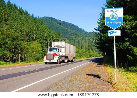 NORTHERN CALIFORNIA, USA - September 3, 2009: Semi truck speeds by a Pacific Coast Scenic Byway sign