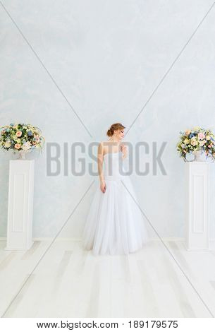 Luxury bride in white dress posing. wedding dress wedding rings wedding bouquet. Beautiful bride with a veil  with white columns