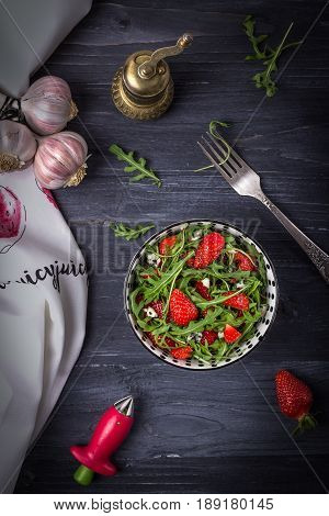 Homemade fresh salad with arugula, strawberries, garlic and cheese roquefort on a dark wooden background. Low key. Top view