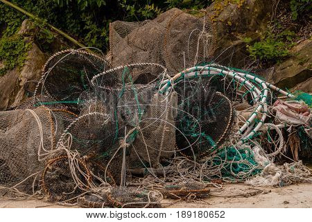 Discarded crab traps and fishing nets piled up in front of large boulders and green foliage.