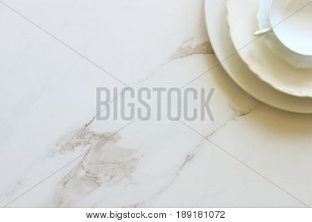 Simple white monochromatic table setting with plates and tea cup. White marble copy space.