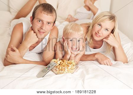 happy family: father, mother and son  relaxing, watching TV and eating popcorn in bed at home