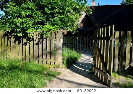 Wide open wooden gate overlooking the garden and country house