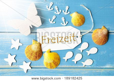 Flat Lay View Of Label With German Text Freizeit Means Leisure Time. Sunny Summer Greeting Card. Butterfly, Shells And Fishes On Blue Wooden Background