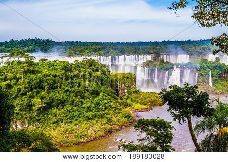 Small boats transport curious tourists to the place where water falls. Iguazu Falls National Park on the border of Argentina, Brazil and Paraguay. The concept of extreme and exotic tourism