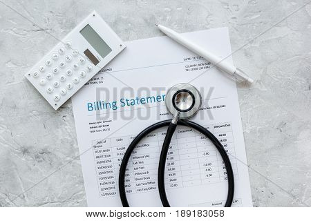 health care costs with billing statement, stethoscope and calculator on stone table background top view