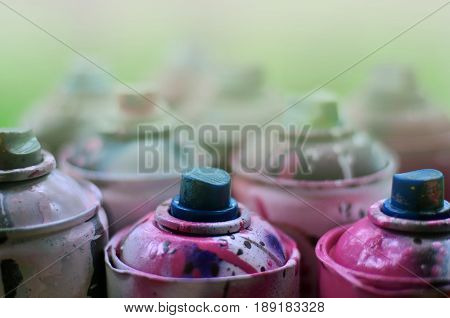 A Lot Of Used Spray Cans Of Paint Close-up. Dirty And Smeared Cans For Drawing Graffiti. The Concept