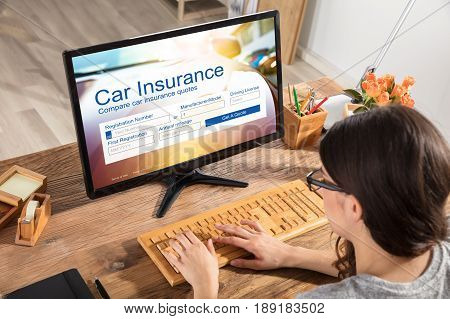 Businesswoman Filling The Car Insurance Form On Computer In Office