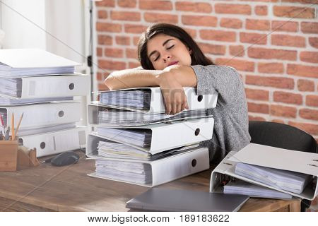 Young Businesswoman Sleeping On Folder Stacked On Office Desk At Workplace