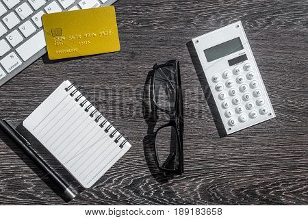 accountant or banker desk with calculator, credit card and keyboard on dark wooden background top view