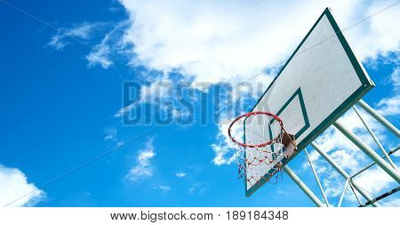 Basketball hoop on a blue sky with clouds. beautiful basketball hoop in the outdoor garden court daylight morning.