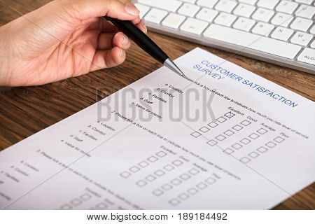 Cross Placed In Excellent Checkbox On Customer Satisfaction Survey Form By A Businessperson
